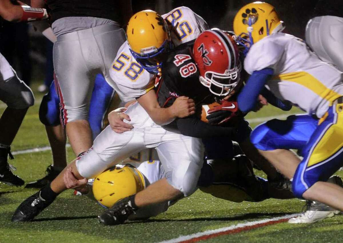 New Canaan's Kevin McDonough, center, is brought down just over the goal line for a touchdown as he is tackled by Seymour defenders including Dylan Sadick, left, during Friday's game at New Canaan High School on October 15, 2010.