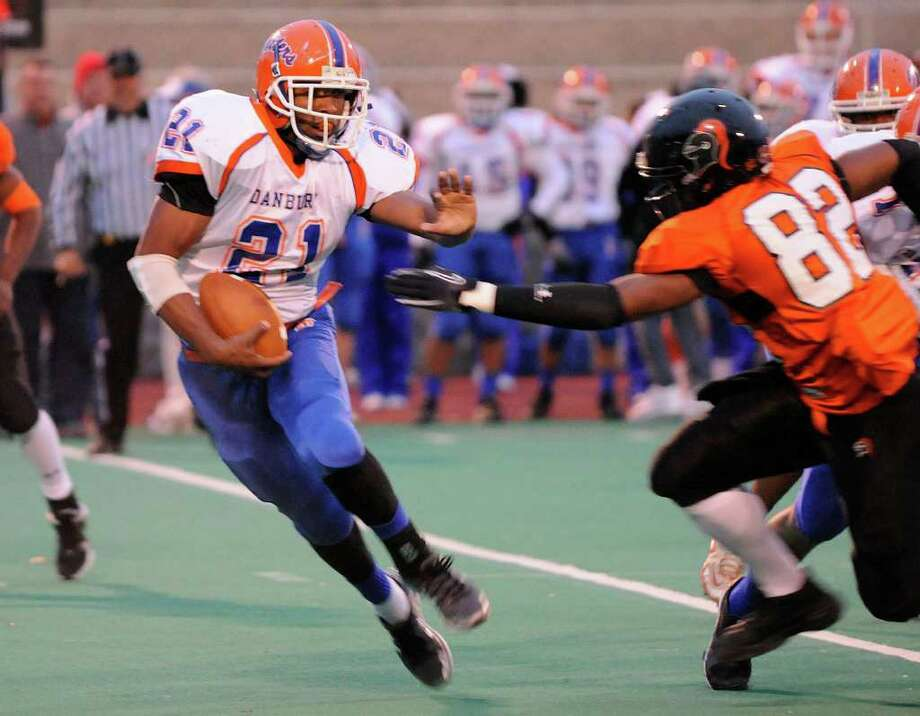 Danbury's Deyon Rosato gains some yardage covered by Stamford's Reuben Pierre-Louis as Stamford High School hosts Danbury High School in varsity football on Friday, October 15, 2010. Photo: Shelley Cryan / Shelley Cryan freelance; Stamford Advocate Freelance