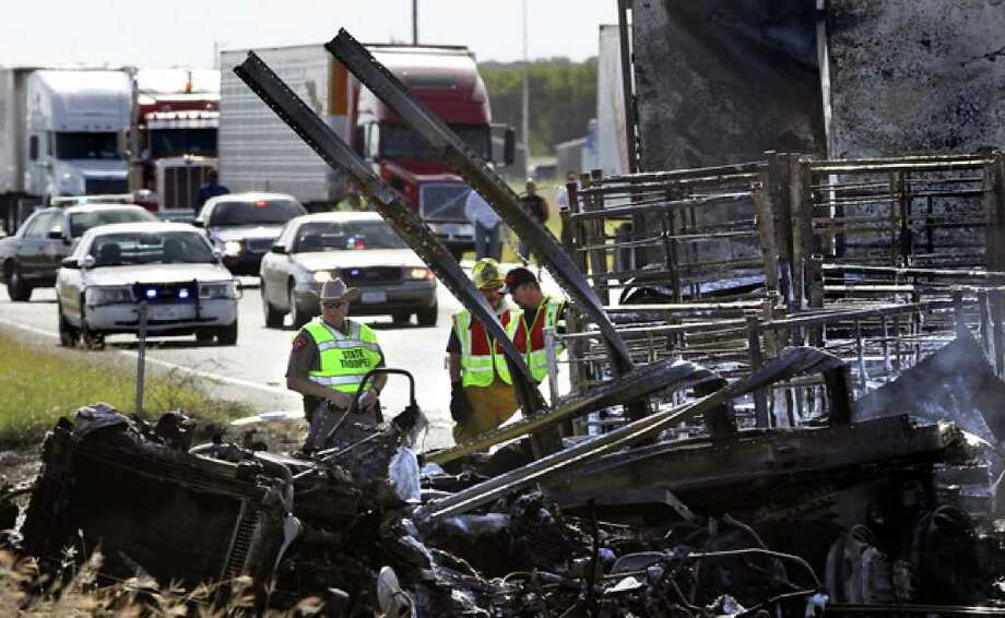 Officials investigate the scene of a fiery wreck that killed two people on Interstate 35 near Lytle.