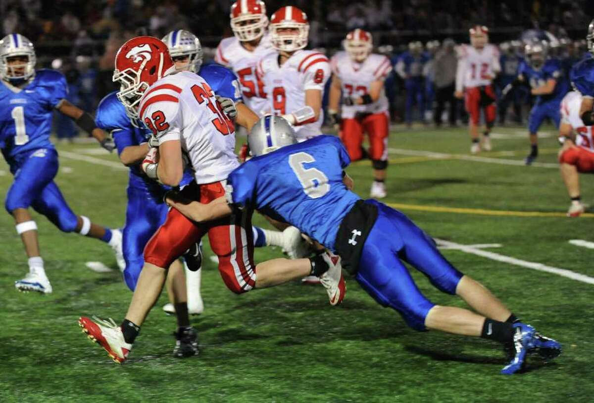 Masuk's #32 Colin Markus gets tackled by Bunnell's #6 Ryan Kelly, during SWC football action in Stratford, Conn. on Friday October 15, 2010.