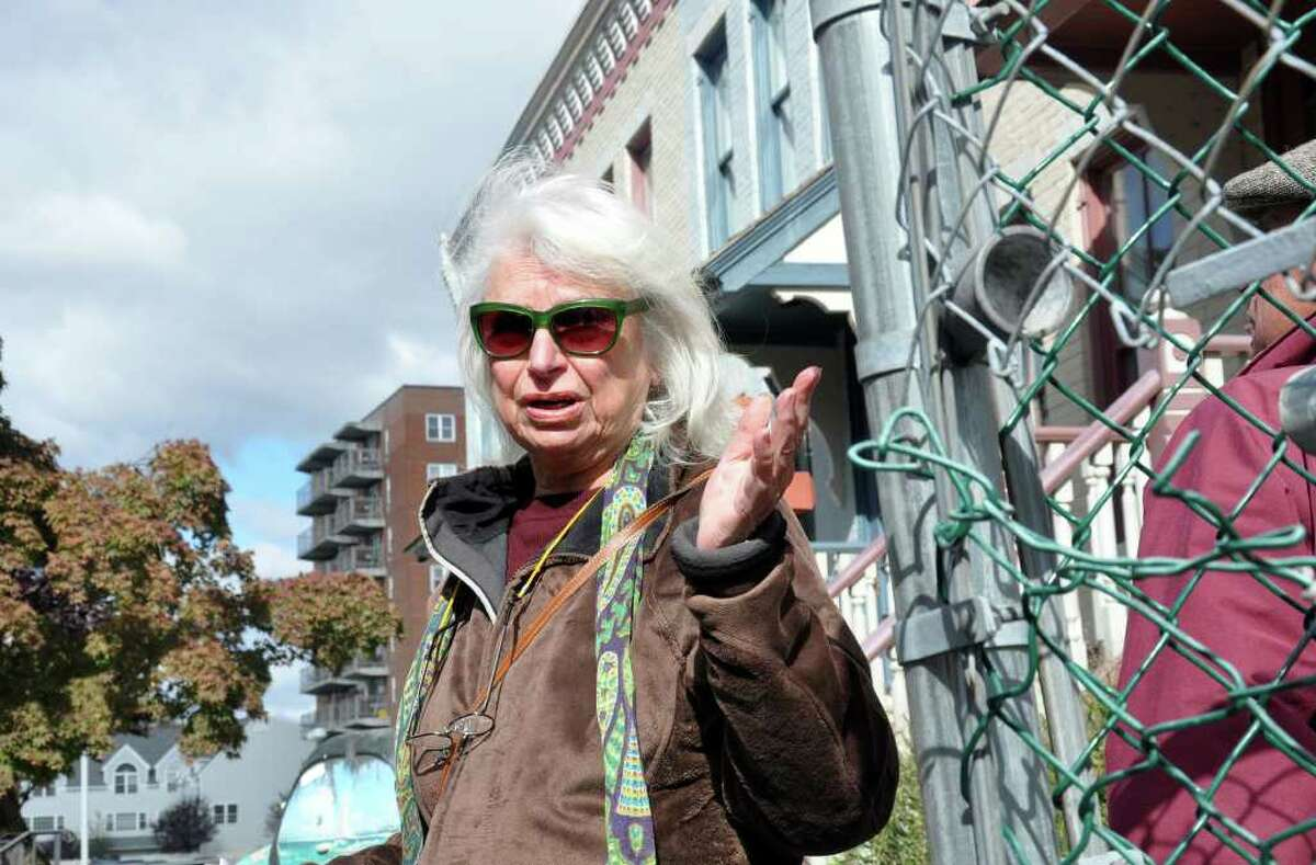Renee Kahn, artist and architectural historian, stands in front of row houses on Franklin Street as she speaks about the chain link fences that surround buildings in downtown Stamford during a tour of historic downtown Stamford on Saturday, Oct. 16, 2010.