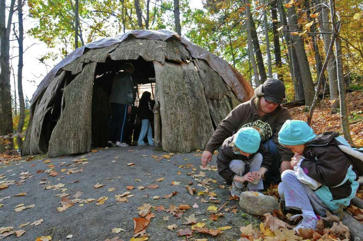 Paige Cook, 5, left, and her sister, Amber, 6, right, and their mom, Renee Breedon, grind corn into meal Sunday outside of a wigwam covered in elm bark, during Native New York Family Day at Brookside Museum in Ballston Spa. ( Philip Kamrass / Times Union )