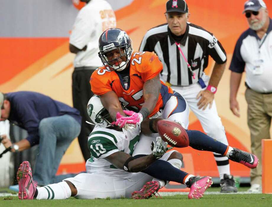 Denver Broncos safety Renaldo Hill (23) breaks up a pass intended for New York Jets wide receiver Santonio Holmes (10) during the second half of an NFL football game Sunday, Oct. 17, 2010, in Denver. (AP Photo/Barry Gutierrez) Photo: AP