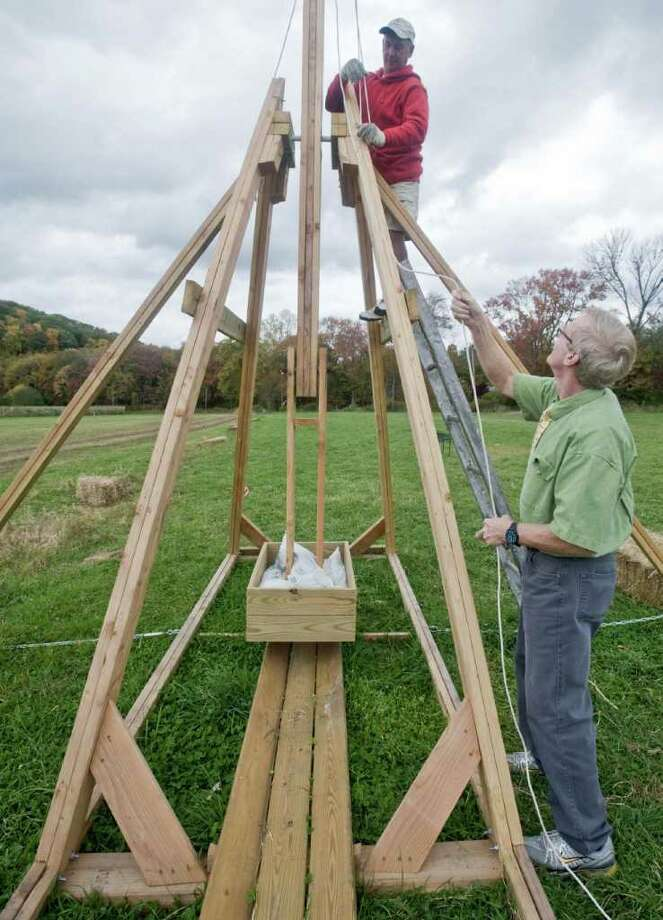 Newtown's Castle Hill Farm owner Steve Paproski works from the ladder as Newtown Middle School teacher Don Ramsey takes up the slack on the harness of a trebuchet, a medieval hurling machine that will launch pumpkins at the farm. Photo taken Thursday, Oct. 14, 2010 Photo: Scott Mullin / The News-Times Freelance