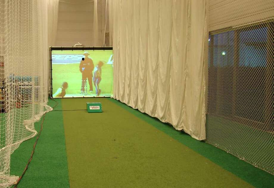 A cricket bowler prepares to deal on-screen at ProBatter in Milford, which is selling its baseball pitching simulators, with the sport-appropriate changes, into the cricket market. Photo: Contributed Photo / Stamford Advocate Contributed