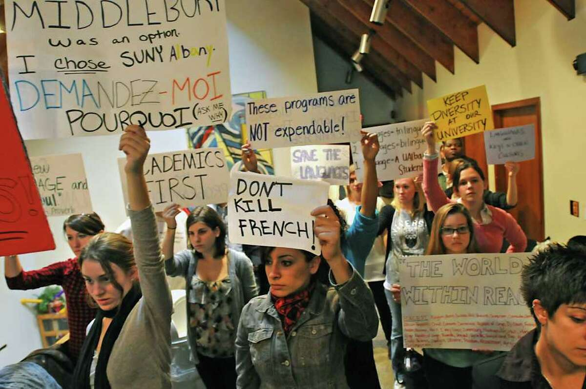 Protesters hold up signs in the back of a meeting room where a Faculty Senate meeting was going on in the Alumni House at UAlbany in Albany, NY on Monday, October 18, 2010. (Lori Van Buren / Times Union)