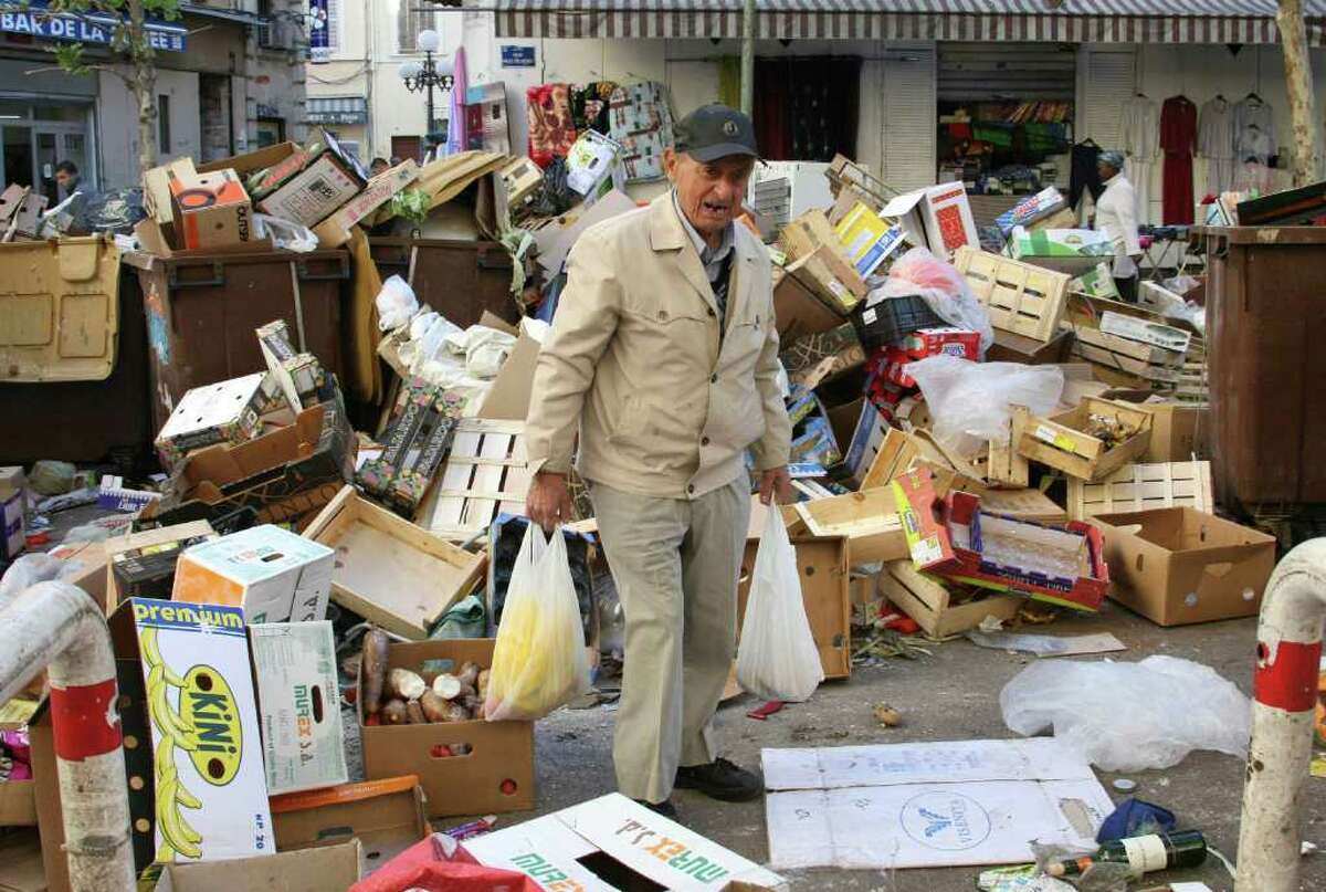 A man makes his way through piles of garbage in Marseille, southern France, Monday Oct.18, 2010. French oil workers on Monday defied the government's demand to get back to work and end scattered fuel shortages, stepping up their fight against President Nicolas Sarkozy's plan to raise the retirement age to 62. Schools, trains, public transport and even garbage collection in Marseille have been blocked by strikes to pressure Sarkozy to back down. (AP Photo/Claude Paris)