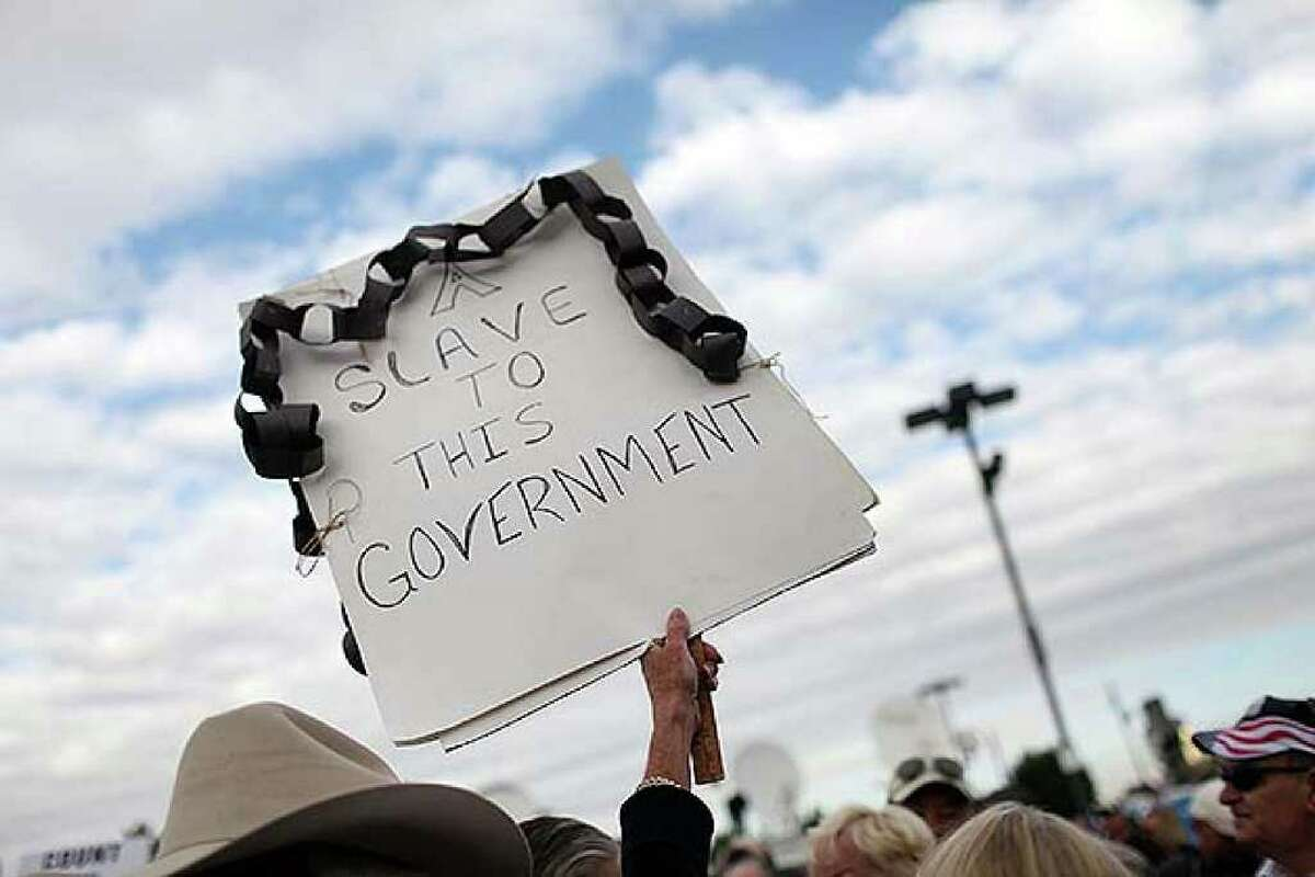 RENO, NV - OCTOBER 18: Tea Party supporters hold up signs while listening to speakers during the launch for the Tea Party Express national tour which kicked off with a rally in Reno on October 18, 2010 in Reno, Nevada. The tour, part of an initiative to get conservatives elected to the House and Senate, will move across country and conclude on November 1, 2010 in Concord, New Hampshire the day before the contentious Mid-Term elections. (Photo by Spencer Platt/Getty Images)