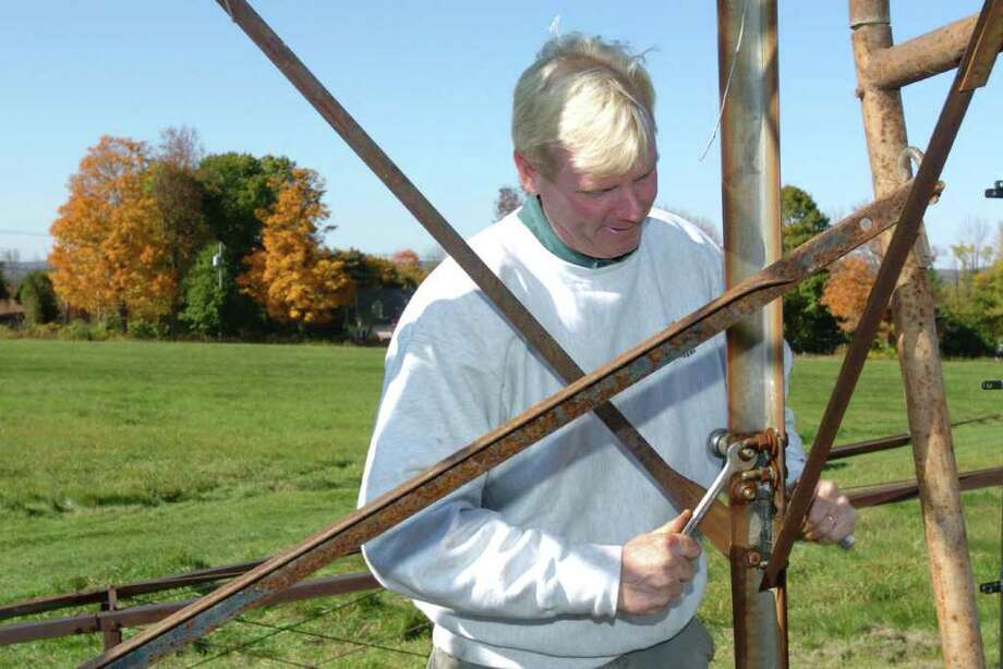 Eugene Reelick, of Hollandia Nursery in Bethel, disassembles a windmill at Happy Landings open space in Brookfield, Oct. 19, 2010. The windmills are considered a local landmark, but were falling into disrepair. They will soon be repainted and placed back. Photo: Chris Ware / The News-Times