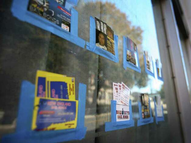 Bail bondsmen keep their cards taped to a storefront window across the street from the courthouse on Golden Hill Street in Bridgeport. Photo: Brian A. Pounds / Connecticut Post