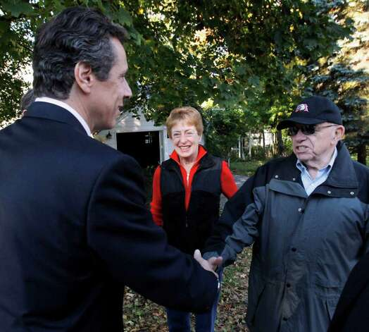 New York Democratic gubernatorial candidate Andrew Cuomo, left, greets Jerry and Vicki Greenberg outside their home before a campaign event where he discussed a property tax cap in Poughkeepsie, N.Y., Tuesday, Oct. 19, 2010.  (AP Photo/Mike Groll) Photo: Mike Groll