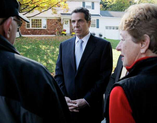 New York Democratic gubernatorial candidate Andrew Cuomo, center, talks with Jerry and Vicki Greenberg outside their home before a campaign event where he discussed a property tax cap in Poughkeepsie, N.Y., Tuesday, Oct. 19, 2010.  (AP Photo/Mike Groll) Photo: Mike Groll