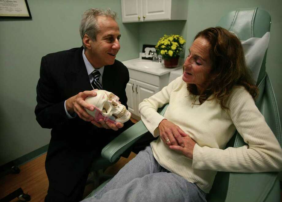 Dr. Bruce Sofferman, left, meets with patient Susan DeFala of Derby at Sofferman Sleep & TMJ Solutions at 63 Elizabeth Street in downtown Derby on Wednesday, October 20, 2010. DeFala suffered from debilitating headaches that she says have stopped since Sofferman's treatments. Photo: Brian A. Pounds / Connecticut Post