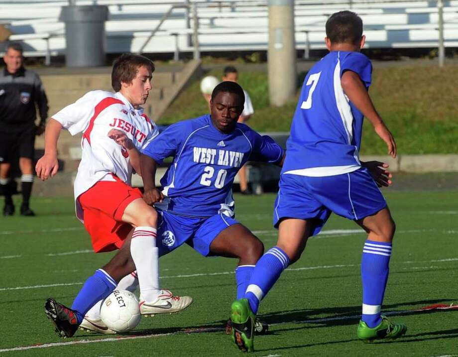 Fairfield Prep's David Bruton, left, and West Haven's Jorge Ardon, center, fight for control of the ball during Tuesday's game against West Haven at Fairfield University on October 19, 2010. Photo: Lindsay Niegelberg / Connecticut Post