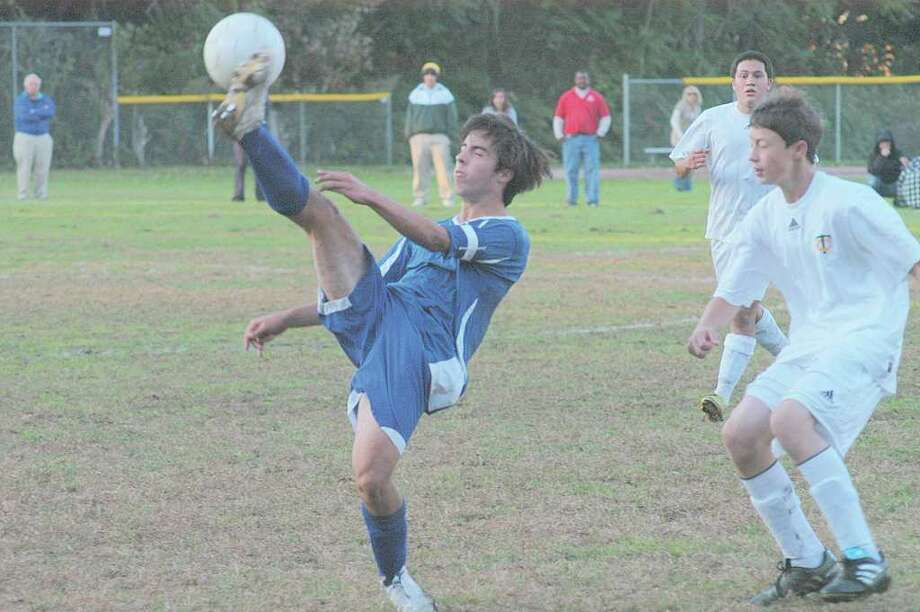 Darien's Alex McGuire gets acrobatic as he tries to pass off the ball behind him, to his teammates. Photo: Contributed Photo / Darien News