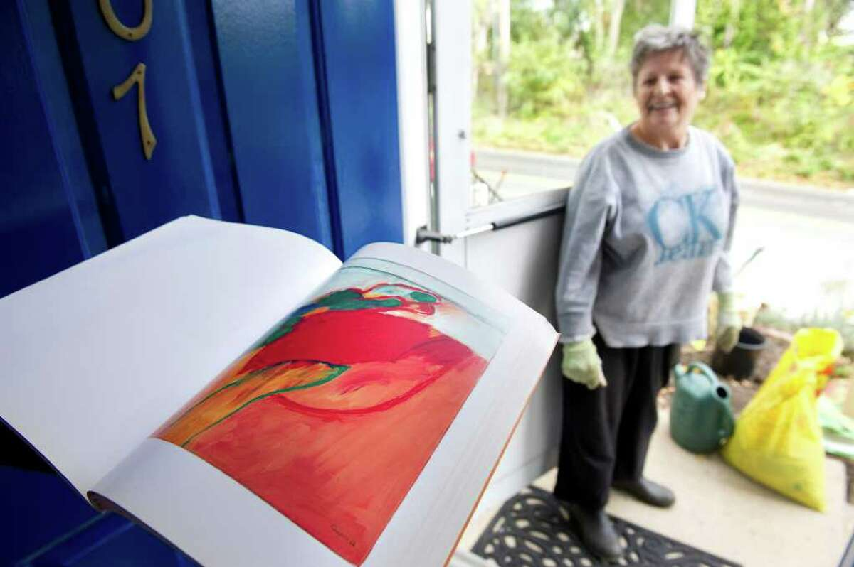 Blanche Shapiro, who grew up in France and moved to Connecticut in 1969, takes a break from gardening to show off her late husband's art work at Waterside Green in Stamford, Conn. on Wednesday October 20, 2010.