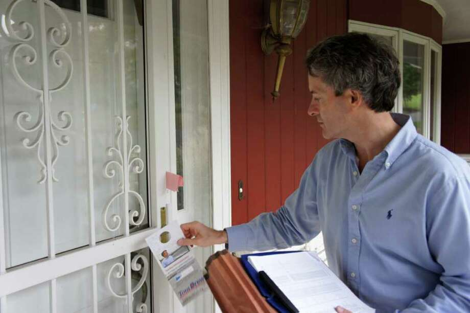 State Rep. Tom Drew, D-132, leaves a campaign flyer for a resident in the Stratfield neighborhood of Fairfield while campaigning on Wednesday, Oct. 20, 2010. Photo: Paul Schott / Fairfield Citizen