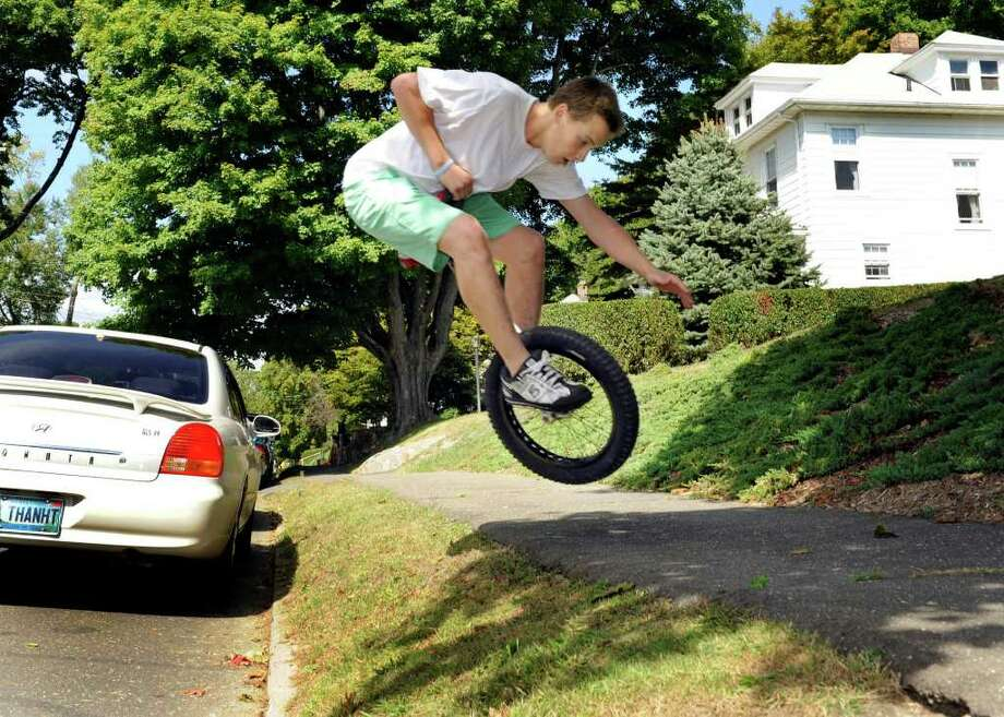 Will Riley jumps onto a sidewalk near his home while riding his unicycle. Photo: Carol Kaliff / The News-Times