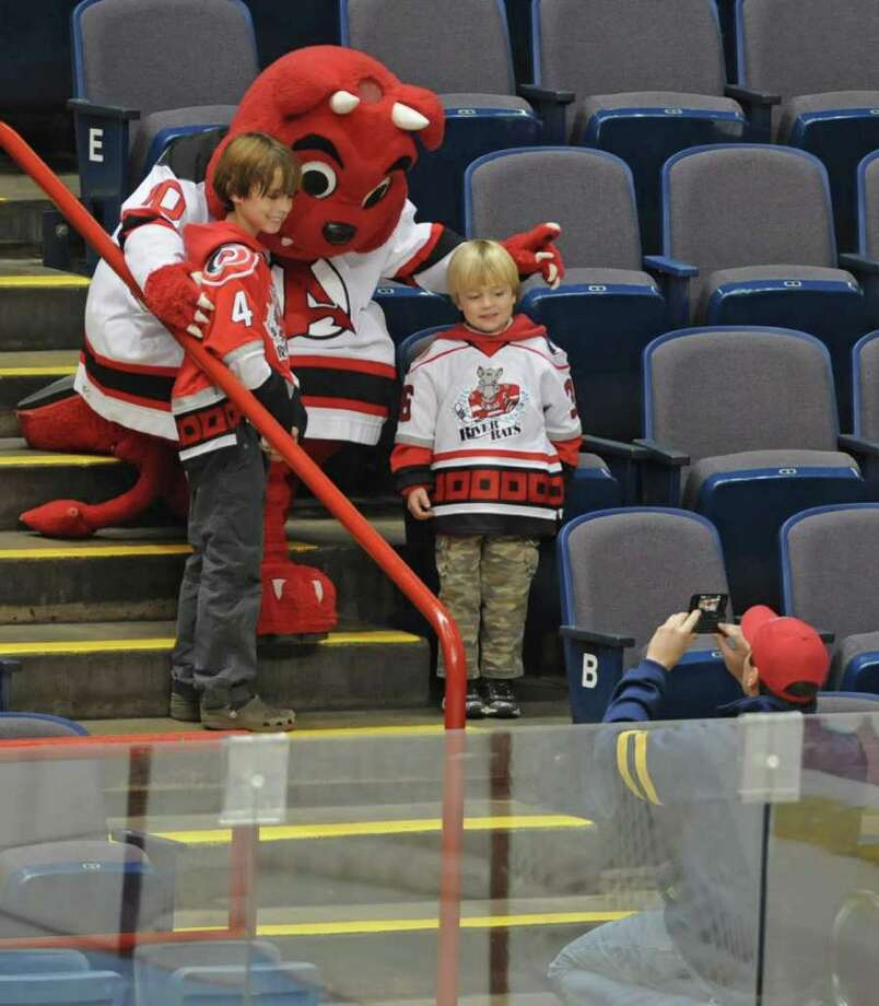 Rowdy the River Rat was replaced as mascot by the Albany Devil Dog.  Mike Ripley of Albany takes a photo of his sons Jack, 9, left, wearing a Albany Devils jersey and Pierce, 5, wearing an Albany River Rats jersey with the Albany Devil Dog during the Albany Devils- Charlotte Checkers hockey game. Photo: Lori Van Buren