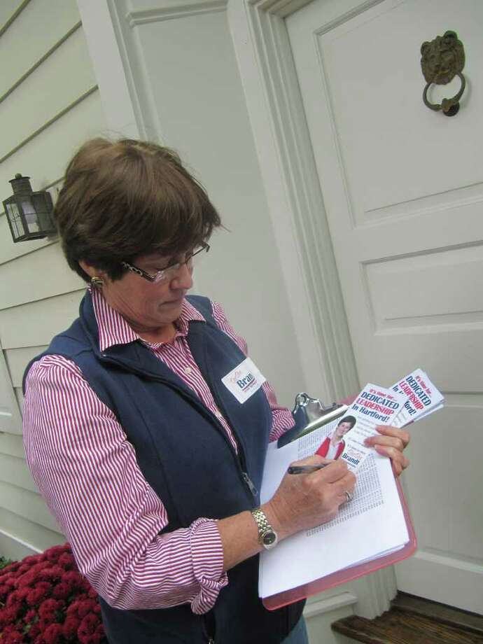 Dee Dee Brandt, state representative candidate for the 133rd Assembly District, walked door-to-door in the Greenfield Hill area Wednesday afternoon. She is pictured at the door of an Old Academy Road home. There was no answer but Brandt left her mark with campaign literature. Photo: Kirk Lang / Fairfield Citizen