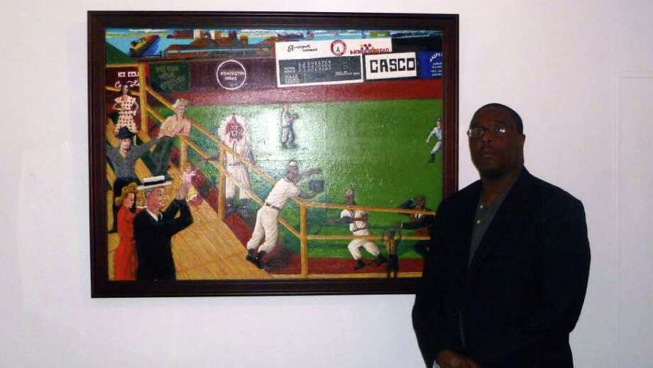 """Duane Corey, a Fairfield University public safety officer, stands next to his painting, """"Shadow Ball in Jasper's Town,"""" part of an exhibition of his work at the school's Lukacs Gallery. The paintings tell the story of Negro League baseball in Bridgeport and the United States."""