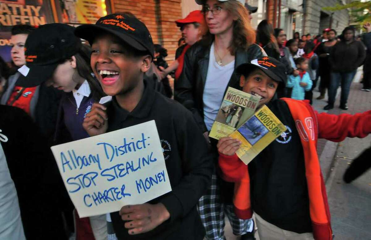 """Charter school students Naszahliek Giggetts, left, and Armando Butler, right, both 11, enjoy themselves while waiting to enter the Palace Theatre to see """"Waiting for Superman"""" on Wednesday. (Philip Kamrass / Times Union)"""