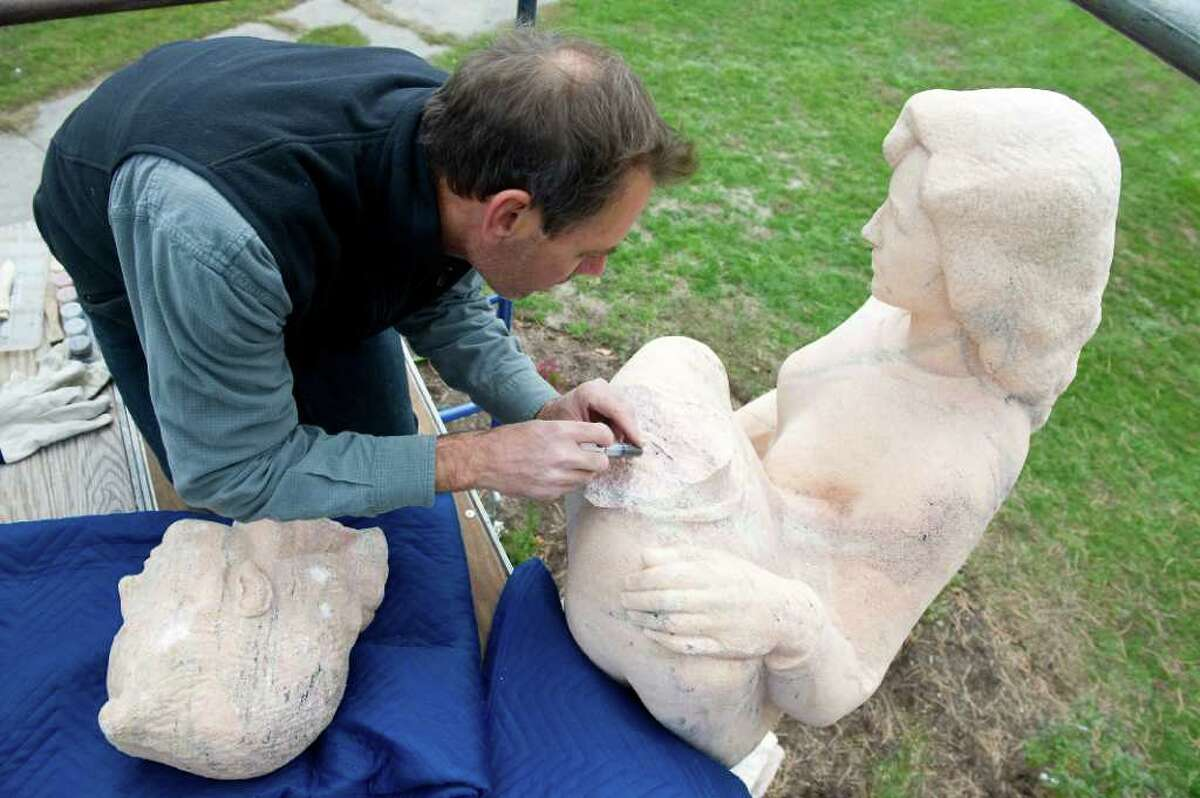 Francis Miller, of ConservArt of Hamden, repairs the damaged statue of two women embracing in Czescik Park in Stamford, Conn. on Friday October 22, 2010.
