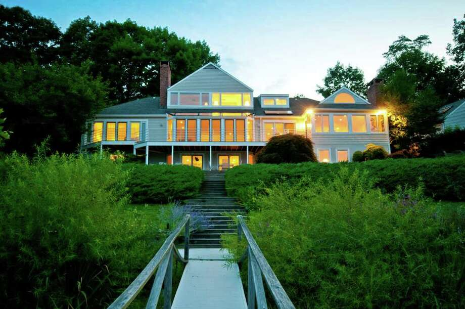 The contemporary house at 39 Cavalry Road in Weston will be auctioned on Friday, November 4 at 11 am on site. Selling at absolute auction,there is no reserve price, and the almost 5,000 square-foot house will go to the highest bidder. The three-level home on more than two acres sits on a slight slope above Crystal Lake and has a private dock and beach rights.There are water views from almost every room, walls of windows, four bedrooms, five full baths, three fireplaces and a three-car garage. Photo: Contributed Photo / Stamford Advocate Contributed