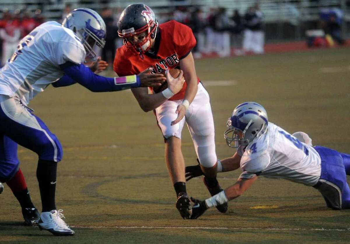 McMahon's Zack O'Connor is tackled by Fairfield Ludlowe's Nick Fernandes, right,a nd Tom Hammons, left, during Friday's game at Brien McMahon High School on October 22, 2010.