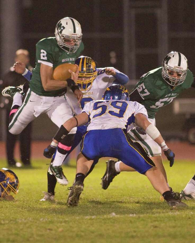 New Milford quarterback Karl Bradshaw (2) goes airborne, but Brookfield's Tyler Heckmann (59) is waiting for him when he comes down Friday night, Oct. 22, 2010, at New Milford High School. Photo: Barry Horn / The News-Times Freelance