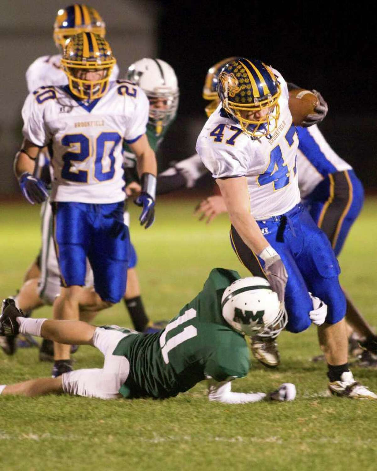 Brookfield's Matt Consalvo breaks a tackle attempt by New Milford's Patrick Jordan and scampers the rest of the way untouched for a touchdown Friday night, Oct. 22, 2010, at New Milford High School.