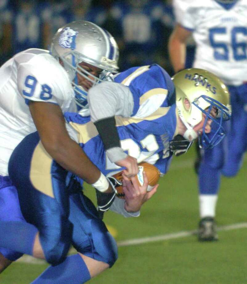 Bunnell's 98, Randy Mallory, tackles Newtown's 26, Brendan McNamara during the football game at Southbury Oct, 22, 2010. Photo: Chris Ware / The News-Times