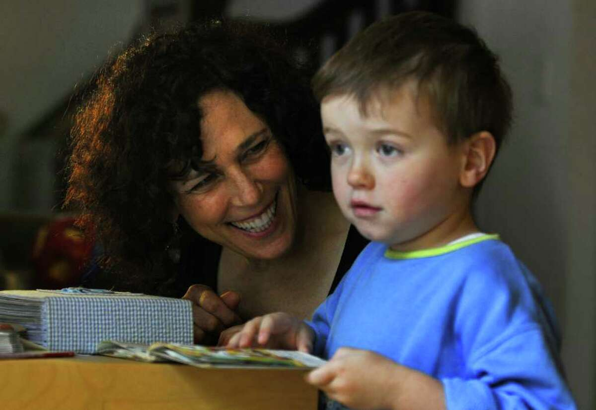 Dance movement therapist Rachelle Smith-Stallman works with 4 year old Emil Bouget as they look at a book together, during a session at his home in Albany, on Tuesday October 19, 2010. Bouget is autistic. ( Philip Kamrass / Times Union )