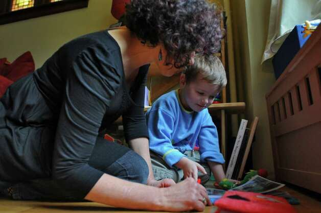 Dance movement therapist Rachelle Smith-Stallman works with 4 year old Emil Bouget , during a session at his home in Albany, on Tuesday October 19, 2010.  Bouget is autistic. ( Philip Kamrass / Times Union ) Photo: Philip Kamrass