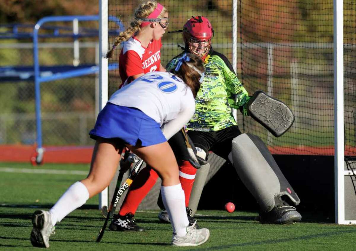 Leslie Gill of Darien High School, # 20, puts a shot on goal that is blocked by Mary Bacon, the GHS goalie, during second half action of the Greenwich High School girls field hockey match vs. Darien High School girls field hockey, at Darien High School, Friday afternoon, Oct. 22, 2010.