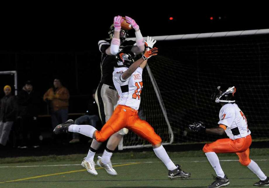 Trumbull #5 Tom Pauciello reaches unsuccessfully for a pass over Stamford's Carlos Martinez as Trumbull High School hosts Stamford High School in Trumbull, CT on Friday, October 22, 2010. Photo: Shelley Cryan / Shelley Cryan freelance; Stamford Advocate Freelance
