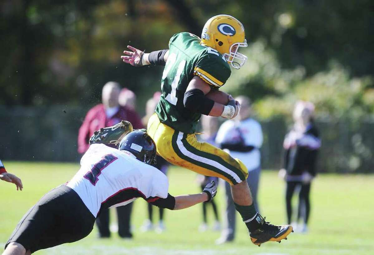 Trinity Catholic High School's Mike Rivas jumps over Fairfield Warde High School's Alan Gray en route to a touchdown in football action in Stamford, Conn. on Saturday October 23, 2010.