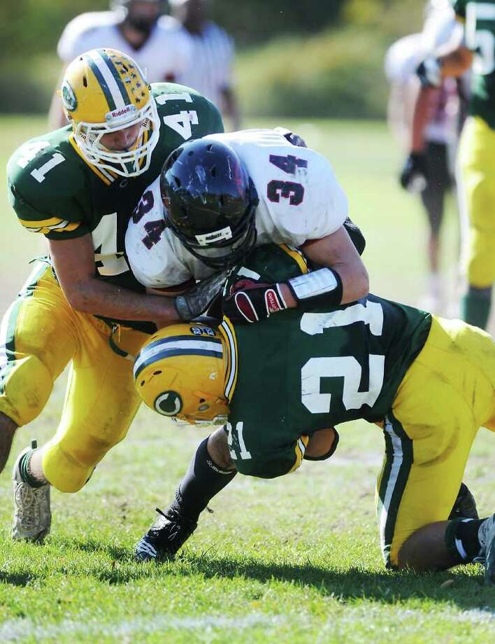 Trinity Catholic High School's Tyler Zaro and Mike Rivas take down Fairfield Warde High School's David Wolff in football action in Stamford, Conn. on Saturday October 23, 2010. Photo: Kathleen O'Rourke / Stamford Advocate