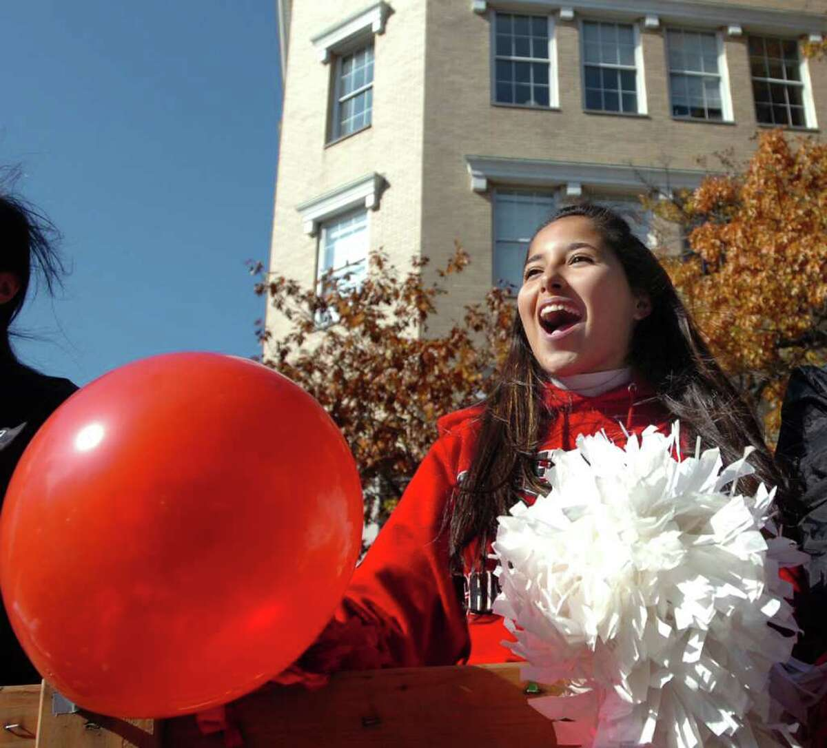 Greenwich High School junior varsity cheerleader Samantha Garcia leads the cheering from the GHS junior varsity float during the Greenwich High School homecoming parade on Greenwich Avenue, Saturday morning, Oct. 23, 2010.
