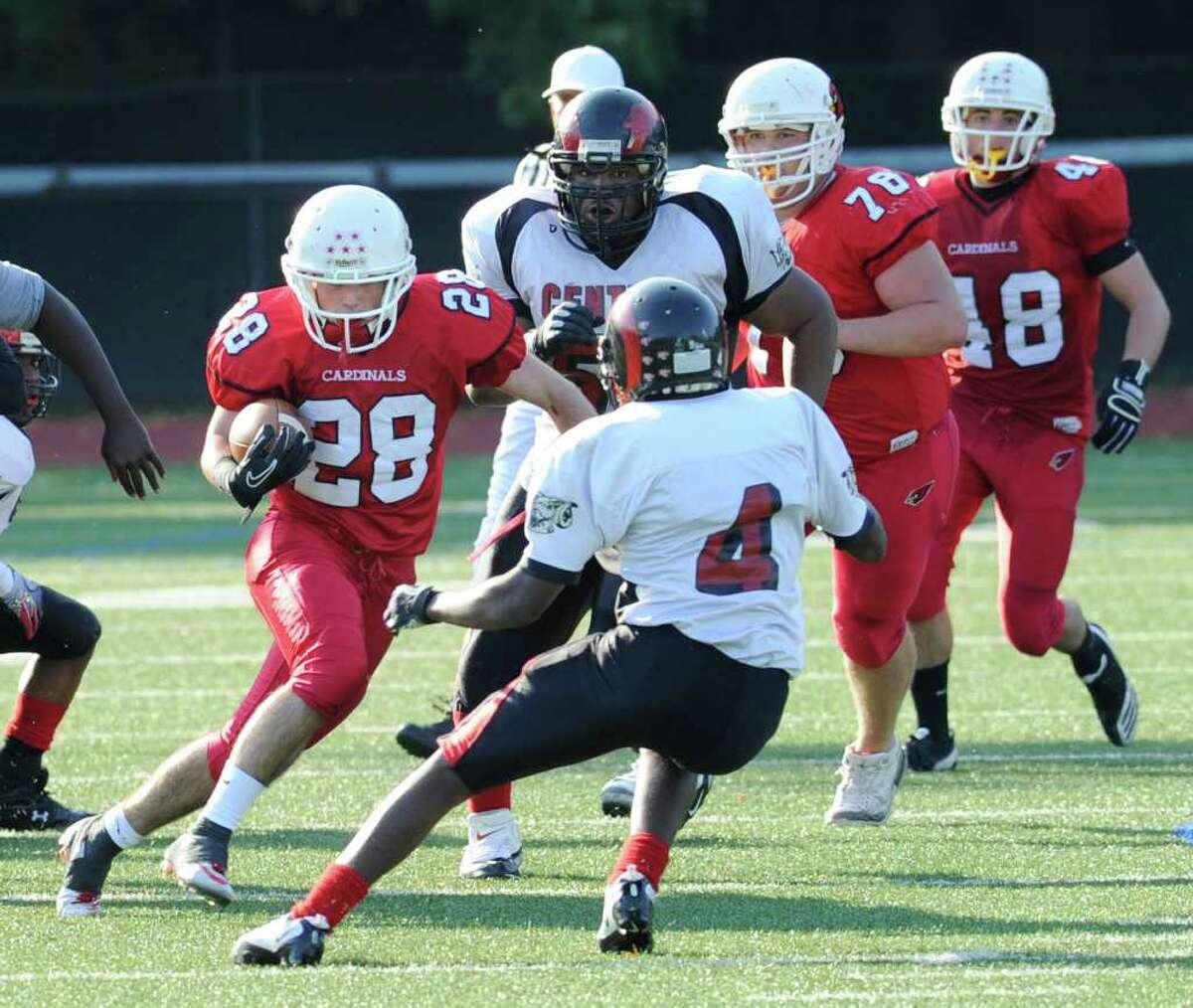 Mark Kelley of Greenwich High School # 28, left, jukes past Chad Lawrence, # 4 of Bridgeport Central, for a 50 yard touchdown run during the third quarter of game at Greenwich High School Saturday, Oct. 23, 2010.