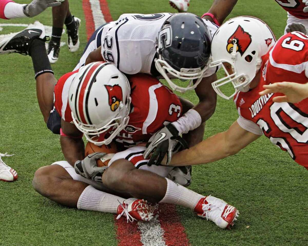 Louisville's Deon Rogers (43) covers the ball after Connecticut's Taylor Mack (29) fumbled a punt during first half action in their NCAA college football game at Cardinal Stadium in Louisville, Ky., Saturday, Oct. 23, 2010. At right is Louisville's Daniel Weedman (60). The fumble led to a touchdown. (AP Photo/Garry Jones)