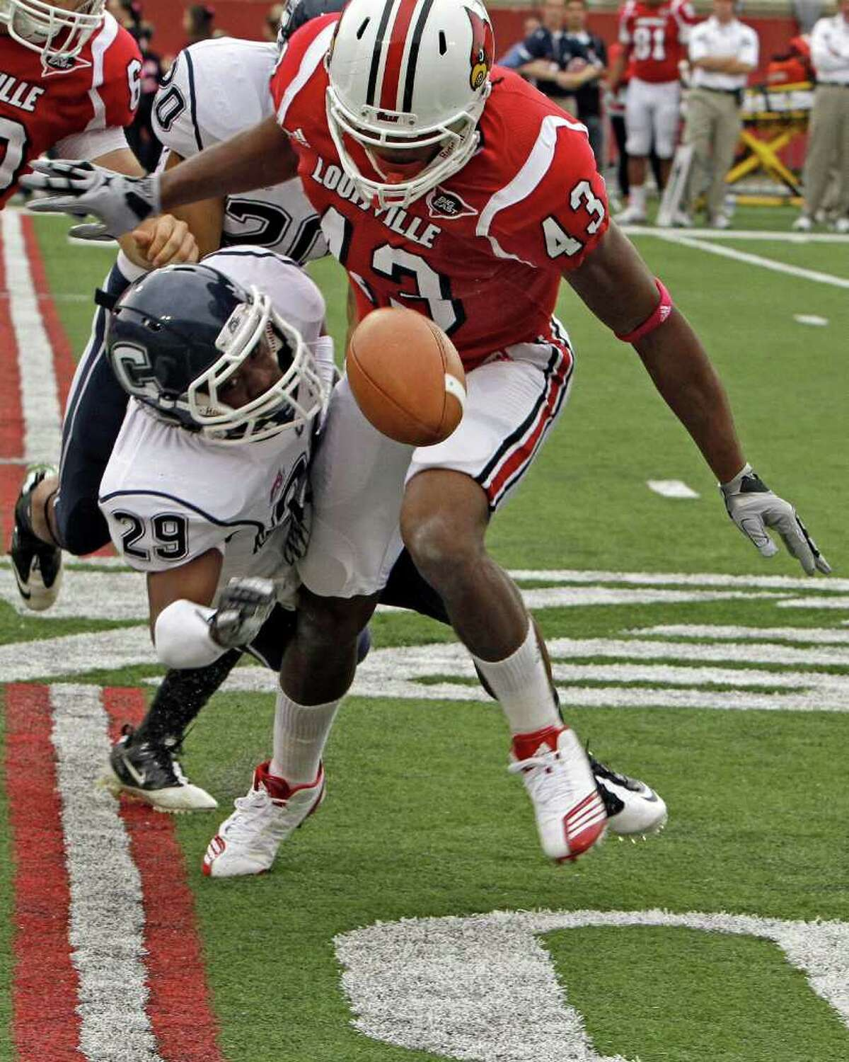 Connecticut's Taylor Mack (29) mishandles a punt and is clobbered by Louisville's Deon Rogers (43) during first half action in their NCAA college football game at Cardinal Stadium, Saturday, Oct. 23, 2010, in Louisville, Ky. Rogers recovered the fumble that led to Louisville first touchdown. (AP Photo/Garry Jones)