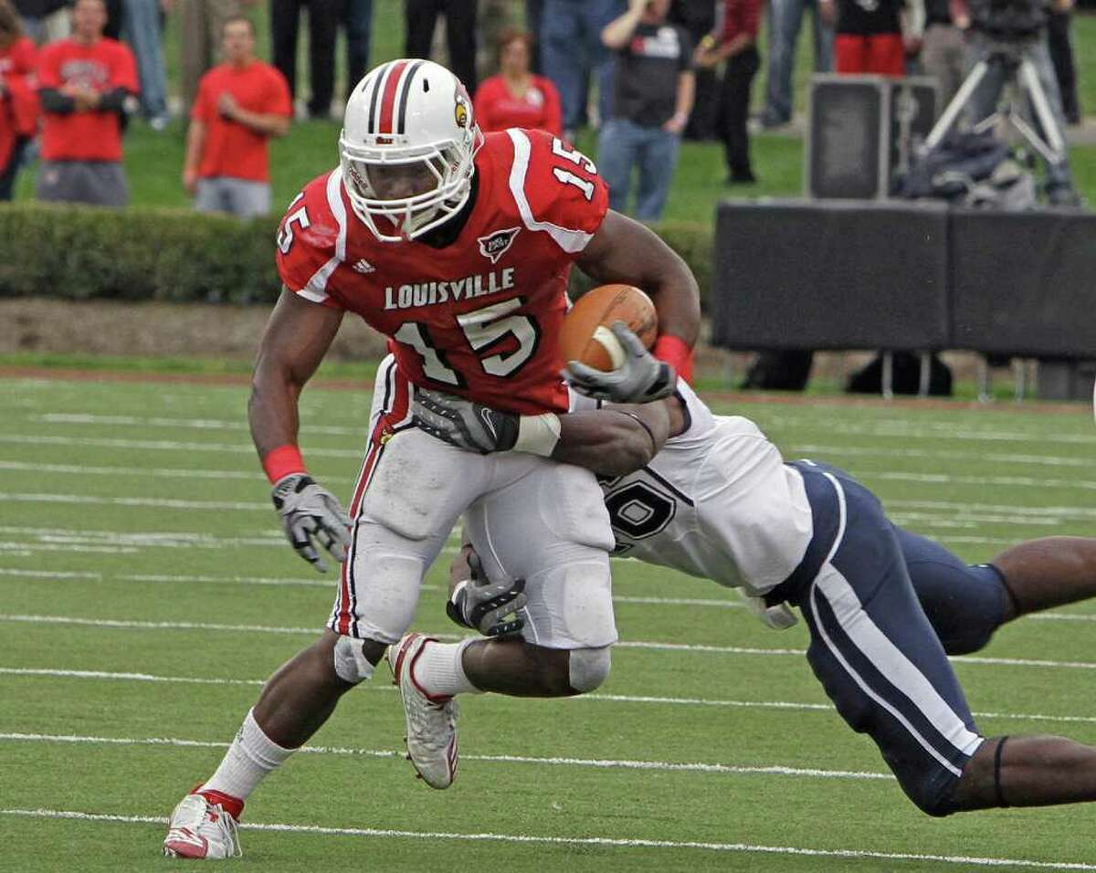Louisville running back Bilal Powell (15) tries to get away from Connecticut's Sio Moore (46) during first half action in their NCAA college football game at Cardinal Stadium, Saturday, Oct. 23, 2010, in Louisville, Ky. (AP Photo/Garry Jones)