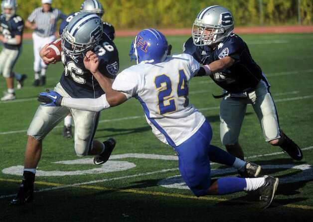 Staples' Jason Kozel is tackled by Harding's TeQuan Broadway during Saturday's game in Westport on October 23, 2010. Photo: Lindsay Niegelberg / Connecticut Post