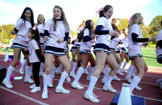 Wearing pink for breast cancer awareness, Staples cheerleaders support their team during Saturday's game against Harding High School in Westport on October 23, 2010. Photo: Lindsay Niegelberg / Connecticut Post