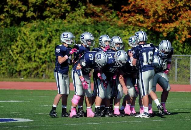 The Staples football team gathers in a huddle during Saturday's game against Harding High School in Westport on October 23, 2010. Photo: Lindsay Niegelberg / Connecticut Post