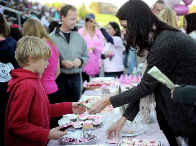 Brian Wilk, 9, left, buys a brownie sold to support breast cancer awareness during Saturday's game at Staples against Harding High School in Westport on October 23, 2010. Photo: Lindsay Niegelberg / Connecticut Post