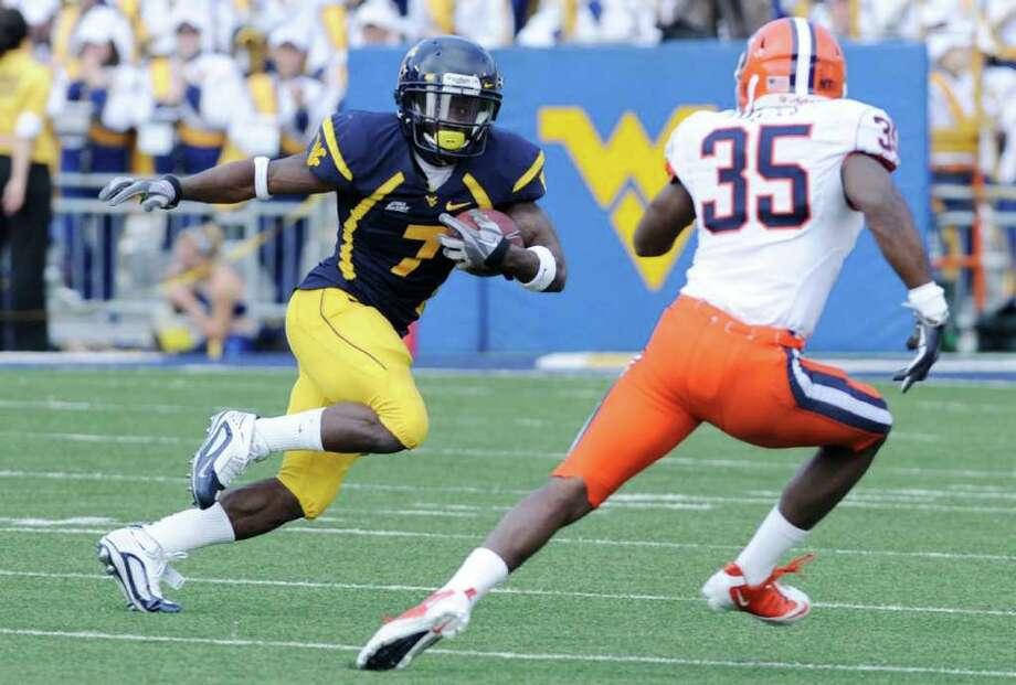West Virginia's Noel Devine looks for running room past Syracuse's Mike Holmes. (AP Photo/Jeff Gentner) Photo: Jeff Gentner