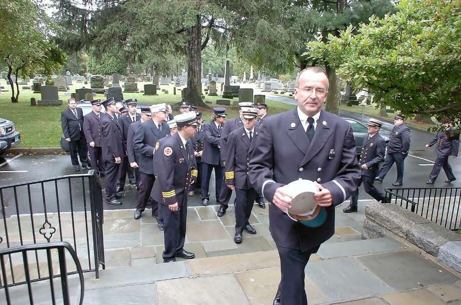 Retired Fire Inspector Chris Doyle leads firefighters into the memorial service Friday afternoon, Sept 11, 2009, at the First Congregational Church on Sound Beach Avenue for Steve Grunow, former volunteer chief for Sound Beach Fire who died Sept. 6, 2009. Doyle and Grunow met in 1975 and volunteered together beginning in 1982. Photo: Keelin Daly / Greenwich Time