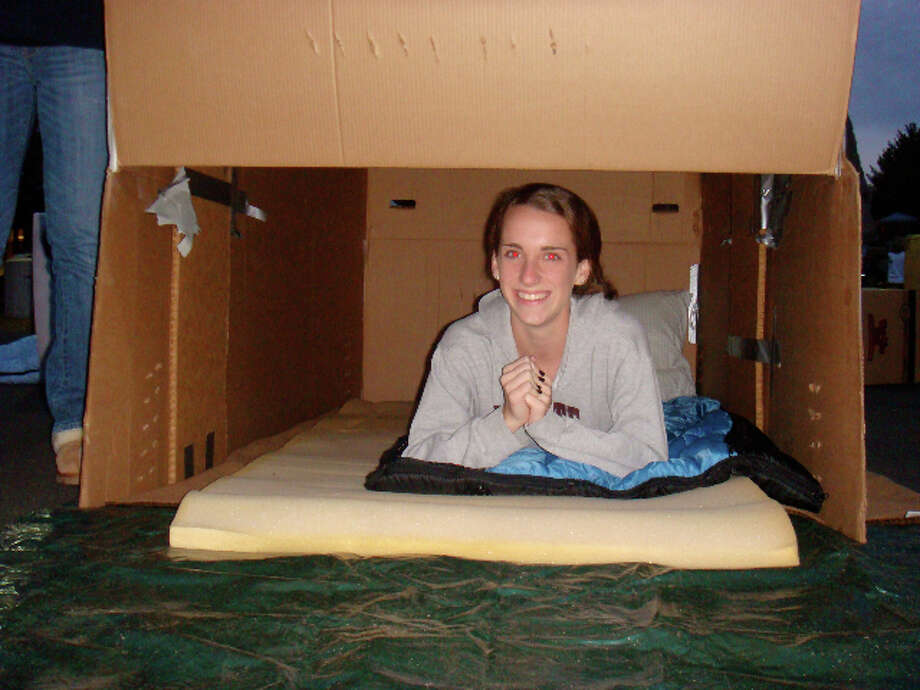 "Emily Hanrahan, a member of St. Luke's youth group, peeks out from her temporary box shelter, which she and others created on Saturday, Oct. 23, 2010, as part of their ""Out of the Box"" project to raise awareness about homelessness in Fairfield County. The group spent the night in the boxes. And is continuing to collect donations for Fairfield-based Operation Hope. Photo: Contributed Photo / Westport News contributed"
